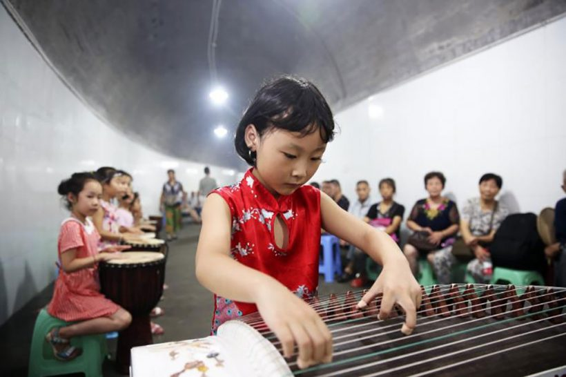 A child plays the guzheng in the north of Chongqing's Beibei District.