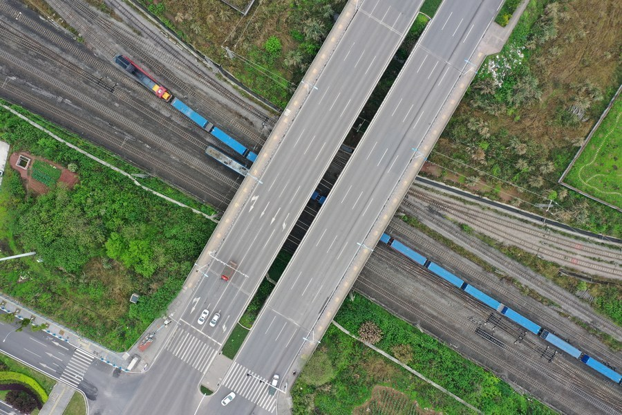Aerial photo taken on March 19, 2021 shows a Yuxinou (Chongqing-Xinjiang-Europe) China-Europe freight train running beneath a bridge in southwest China's Chongqing Municipality. (Xinhua/Tang Yi)